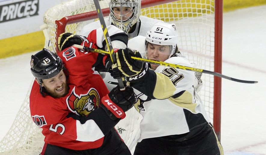 Pittsburgh Penguins' Derrick Pouliot (51) battles Ottawa Senators' Zack Smith (15) in front of Penguins goalie Marc-Andre Fleury during the first period of an NHL hockey game Tuesday, April 7, 2015, in Ottawa, Ontario. (AP Photo/The Canadian Press, Justin Tang)