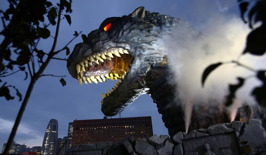 Godzilla's head is unveiled as the irradiated monster was appointed special resident and tourism ambassador for Tokyo's Shinjuku ward during its awards ceremony in Tokyo Thursday, April 9, 2015. The giant Godzilla head towering 52-meters (171 feet) above ground level was unveiled Thursday at an office of Toho, the studio behind the 1954 original. (AP Photo/Shizuo Kambayashi)