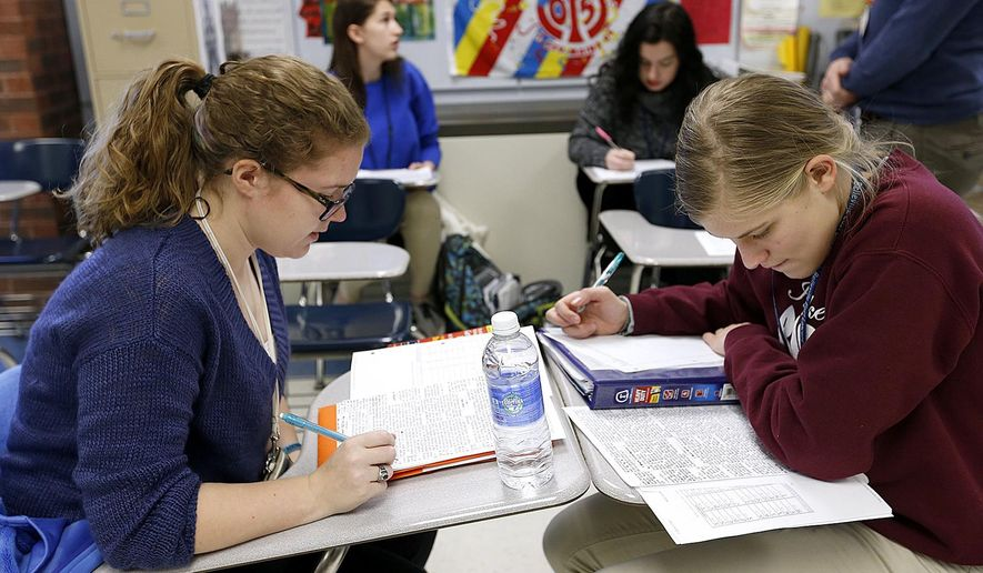 MOVE PHOTO AT 4:00 A.M. CST, THURSDAY, APRIL 9 - In this Feb. 16, 2015 photo, Belleville East High School seniors Peyton Kaercher, left, and Meghan Gingrich work together in their German class to translate the obituary of Peter Geibel who died in 1893 in Belleville, Ill. (AP Photo/Belleville News-Democrat, Steve Nagy)