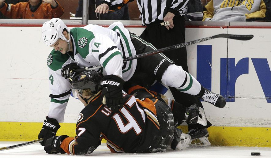 Dallas Stars' Jamie Benn, top, and Anaheim Ducks' Hampus Lindholm, of Sweden, fall to the ice after they collided during the second period of an NHL hockey game, Wednesday, April 8, 2015, in Anaheim, Calif. (AP Photo/Jae C. Hong)