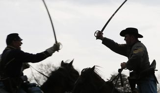 Confederate and Union forces clash during a re-enactment of the Battle of Appomattox Station, Wednesday, April 8, 2015, as part of the 150th anniversary of the surrender of the Army of Northern Virginia to Union forces at Appomattox Court House, in Appomattox, Va. (AP Photo/Steve Helber)