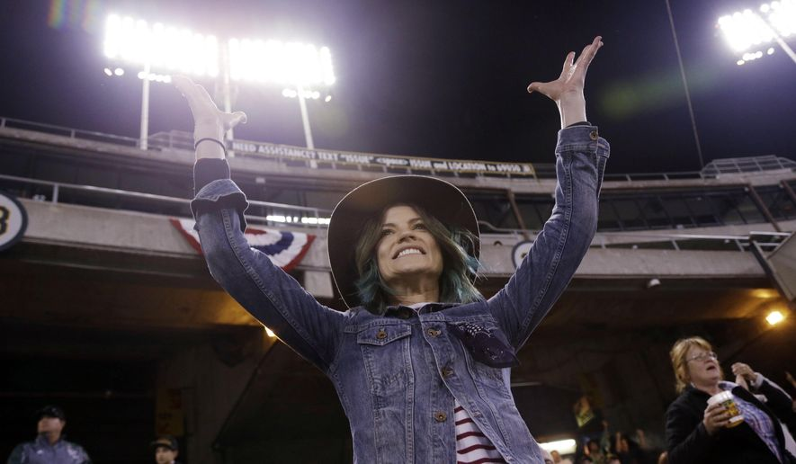 Eireann Dolan, girlfriend of Oakland Athletics relief pitcher Sean Doolittle, cheers during a baseball game between the Athletics and the Texas Rangers on Wednesday, April 8, 2015, in Oakland, Calif. Dolan raised nearly $35,000 to bring LGBT youth to the ballpark for the team's pride night on June 17.  (AP Photo/Marcio Jose Sanchez)