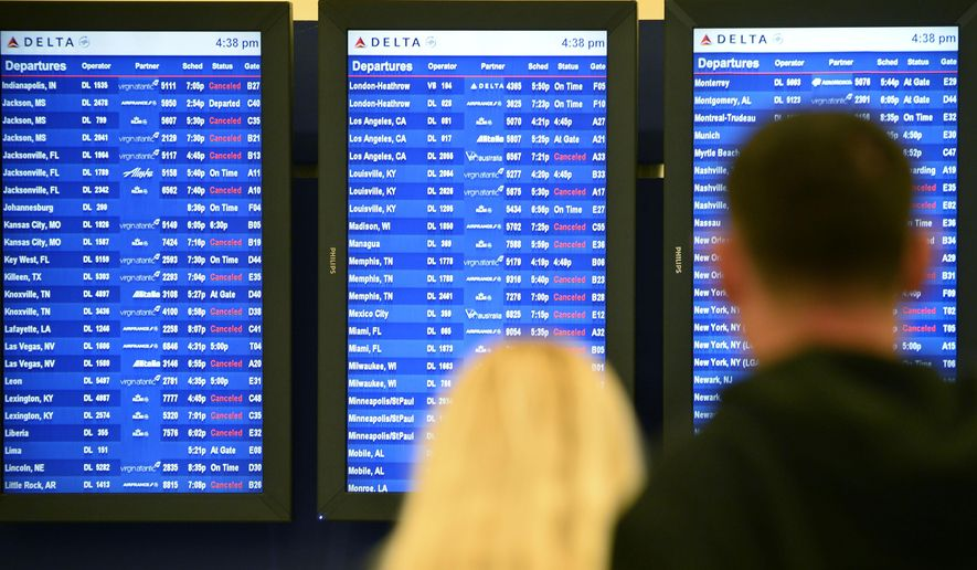 FILE - In this Feb. 25, 2015 file photo, airline passengers look at departure screens with flight cancellations posted as a winter storm bringing a mix of snow, sleet and rain resulted in an FAA-ordered ground stop at Hartsfield-Jackson International Airport in Atlanta. The U.S. Department of Transportation on Thursday, April 9, 2015 said 72.8 percent of flights arrived on time in February, down from 76.8 percent in January but up from 70.7 percent the previous February. (AP Photo/David Tulis, File)