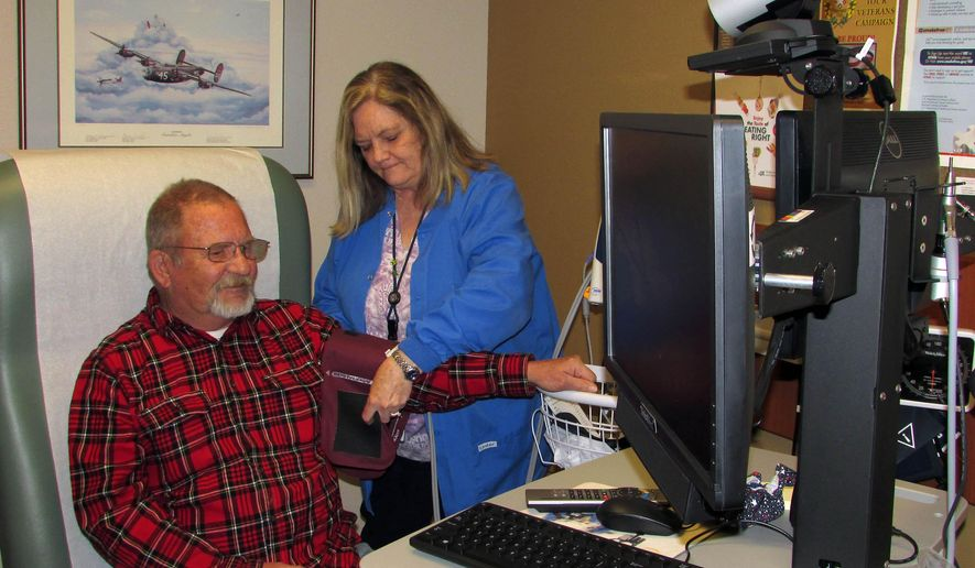 """In this Friday, April 3, 2015 photo, Elko Outreach Clinic nurse manager Janet Peck of the U.S. Department of Veterans Affairs assists Army veteran Earl Bevan in the clinic's tele-health room in Elko, Nev. Bevan, who served in the Vietnam War, said he visits the clinic about once a month. """"This is really, really convenient for me and the other vets,"""" he said. (AP Photo/Elko Daily Free Press, Jeffry Mullins)"""