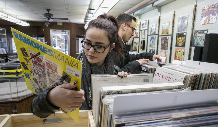 In this March 4, 2015, file photo, vinyl album enthusiasts Brittany Dove, left, and Tyler Lambert browse through the albums at Rich's Record Emporium in downtown Collinsville, Ill. (AP Photo/Belleville News-Democrat, Derik Holtmann) ** FILE **