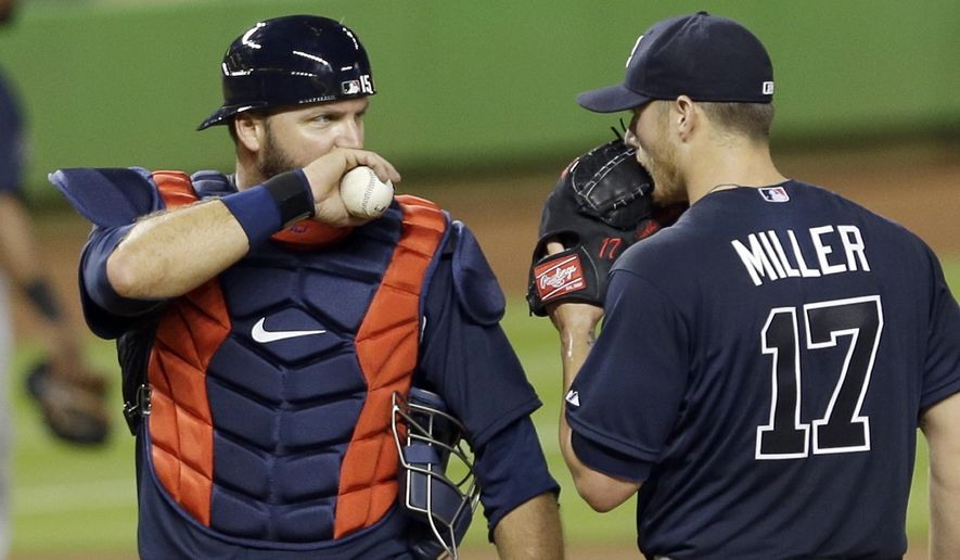 Atlanta Braves catcher A.J. Pierzynski, left, talks to Shelby Miller (17) after Miller gave up an infield hit to Miami Marlins' Christian Yelich (21) in the third inning of a baseball game, Wednesday, April 8, 2015, in Miami. (AP Photo/Alan Diaz)
