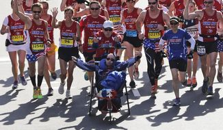 In this April 21, 2014, file photo, Dick Hoyt and Rick Hoyt, from Holland, Mass., cross the finish line surrounded by supporters in the 118th Boston Marathon in Boston. Dick and Rick Hoyt, who over the decades have become among the most recognizable faces of the Boston Marathon, may not be running as a team this year, but they are both very much involved in the festivities. (AP Photo/Charles Krupa, File) **FILE**
