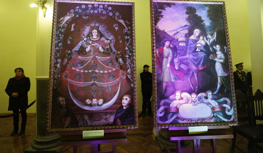 "The paintings ""Virgin of Candelaria,"" and  ""Escape to Egypt,"" are illuminated during a ceremony recognizing their return, at the government palace, in La Paz, Bolivia, Thursday, April 9, 2015. Art collectors Roberta and Richard Huber returned the art work after learning from a museum that the two large paintings had been reported stolen from a Catholic church in southern Bolivia. (AP Photo/Juan Karita)"