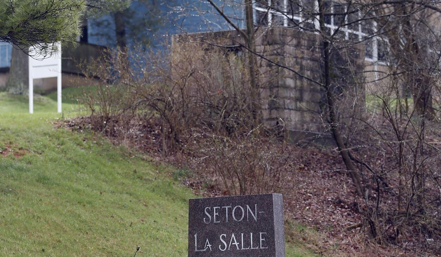 A sign marks the location of Seton-LaSalle High School on Thursday, April 9, 2015 in Mount Lebanon, Pa. The Pittsburgh-area Catholic school was closed for a second straight day while police and the FBI tried to find whoever sent an email threatening to shoot students and staff and which referenced similar incidents at Columbine High School in Colorado and Sandy Hook Elementary School in Connecticut. (AP Photo/Keith Srakocic)