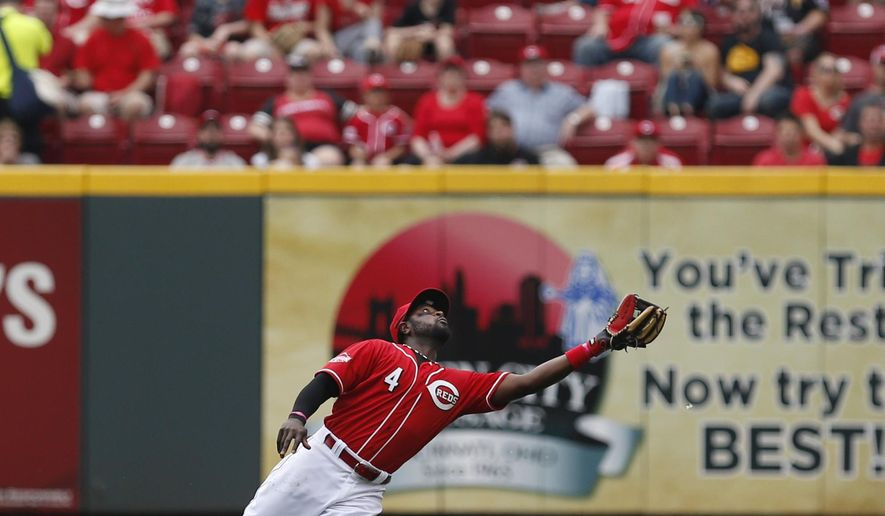 Cincinnati Reds' second baseman Brandon Phillips (4) goes to his knees to catch a ball off the bat of Pittsburgh Pirates' Andrew McCutchen (22) during the fourth inning of their baseball game played Thursday, April 9, 2015 in Cincinnati.  (AP Photo/Gary Landers)