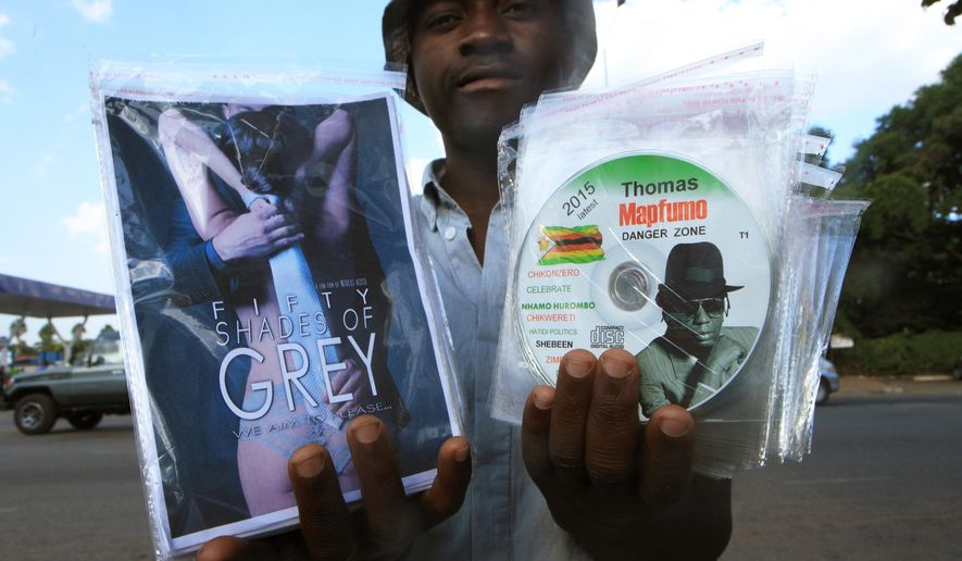 In this photo taken Friday, March 17, 2015 a vendor poses with a fistful of pirated DVDs on sale to passing motorists in central Harare.  The southern African nation's continued economic difficulties have led to such a successful black market of pirated DVDs that many cinemas have been forced to close, and the pirate movies tend not to be censored by the authorities so they are more explicit than the official versions.( AP Photo/Tsvangirayi Mukwazhi)