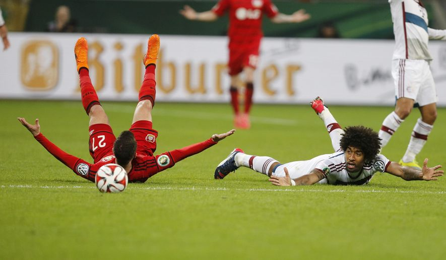 Leverkusen's Gonzalo Castro, left, and Bayern's Dante from Brazil fall during the German soccer cup (DFB Pokal) quarterfinal match between Bayer 04 Leverkusen and Bayern Munich Wednesday, April 8, 2015 in Leverkusen, Germany. (AP Photo/Frank Augstein)