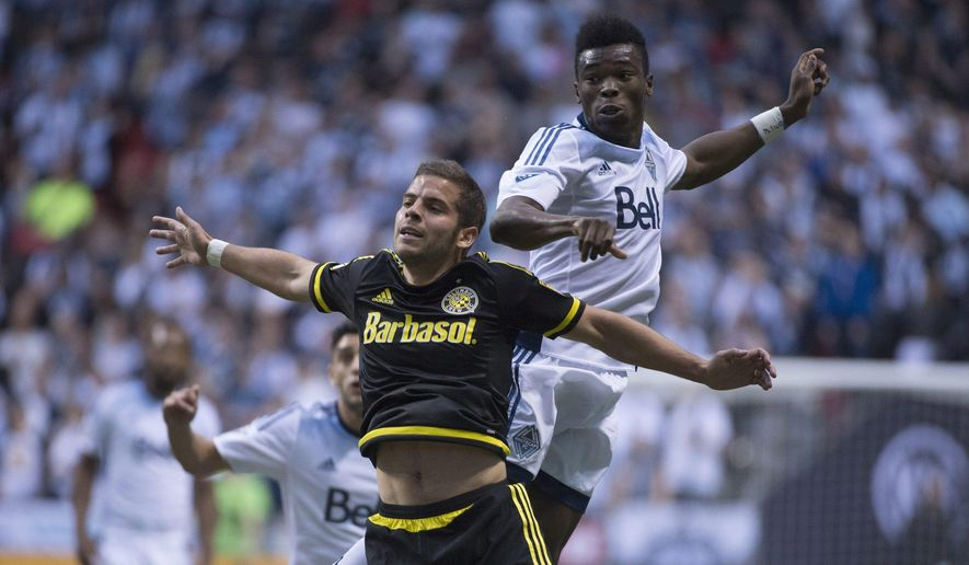 Vancouver Whitecaps FC Sam Adekugbe, right, fights for control of the ball with Columbus Crew SC Ben Speas during the first half of MLS soccer action in Vancouver,  British Columbia, Wednesday, April, 8, 2015. (AP Photo/The Canadian Press, Jonathan Hayward)