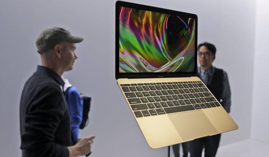 In this March 9, 2015 photo, members of the media and Apple guests get a look at the new MacBook in the demo room after an Apple event in San Francisco. The company will debut the new laptop on Friday, April 10, 2015. (AP Photo/Eric Risberg, File)