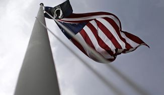 In this March 11, 2015 photo, U.S. and POW-MIA flags fly on the grounds of the Fayetteville Veterans Affairs Medical Center in Fayetteville, N.C. (AP Photo/Patrick Semansky)