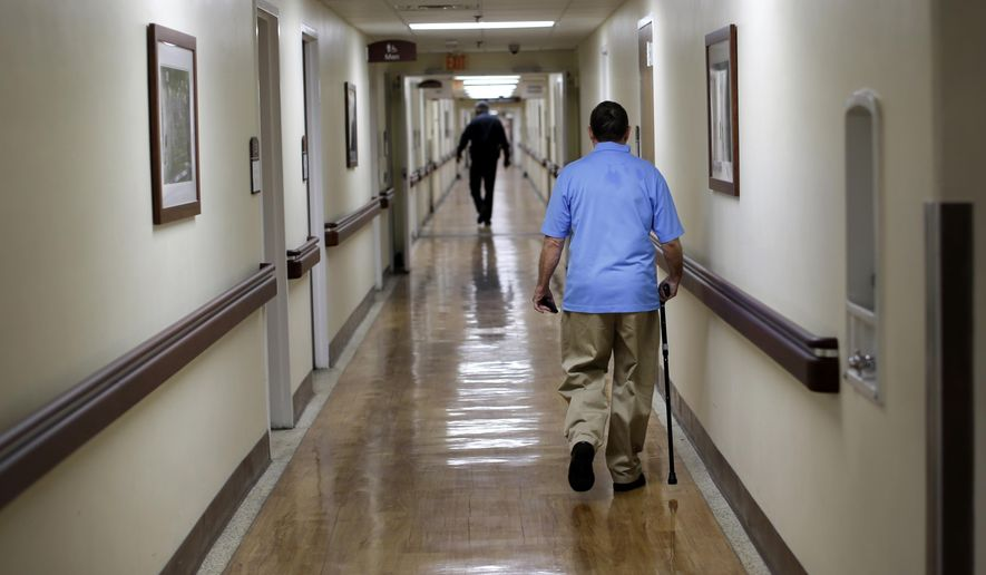 A patient walks down a hallway at the Fayetteville Veterans Affairs Medical Center in Fayetteville, N.C., on March 11, 2015. The VA hospital is one of the most backed-up facilities in the country. (Associated Press) **FILE**