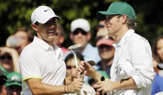Rory McIlroy, of Northern Ireland, hands Niall Horan from the band One Direction a club during the Par 3 contest at the Masters golf tournament Wednesday, April 8, 2015, in Augusta, Ga. (AP Photo/Matt Slocum)