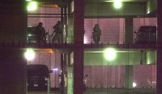 Police search a parking garage on the U.S. Census Bureau headquarters campus Thursday for an armed man who, according to a fire official, shot a security guard at a gate to the facility in Suitland, Md. (Associated Press)