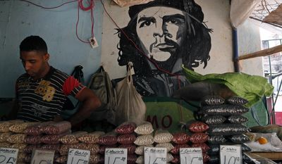 """A man works at a bean stall at a market beside a mural with the a picture of  revolution hero Ernesto """"Che"""" Guevara in Havana, Cuba, Thursday, April 9,  2015.  President Barack Obama signaled Thursday he will soon remove Cuba from the U.S. list of state sponsors of terrorism, boosting hopes for improved ties as he prepared for a historic encounter with Cuban President Raul Castro during the Summit of the Americas taking place in Panama. .(AP Photo/Desmond Boylan)"""