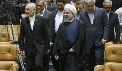 Iranian President Hassan Rouhani (center) arrives to attend a ceremony in Tehran on April 9, 2015, marking National Nuclear Technology Day, as he is accompanied by head of Iran's Atomic Energy Organization Ali Akbar Salehi (left) and Vice President for Science and Technology Affairs Sorena Sattari (right). (Associated Press) **FILE**
