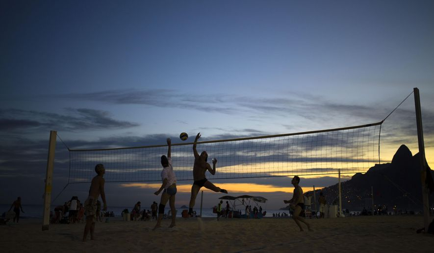 FILE - In this May 1, 2014 file photo, people play beach volleyball on Ipanema beach in Rio de Janeiro, Brazil. This is a late-night town, and the schedule for the Rio de Janeiro's 2016 Olympics are a reflection. The men's and women's beach volleyball finals on famous Copacabana Beach will wrap up about 1:30 a.m., if everything runs on schedule. (AP Photo/Hassan Ammar, File)