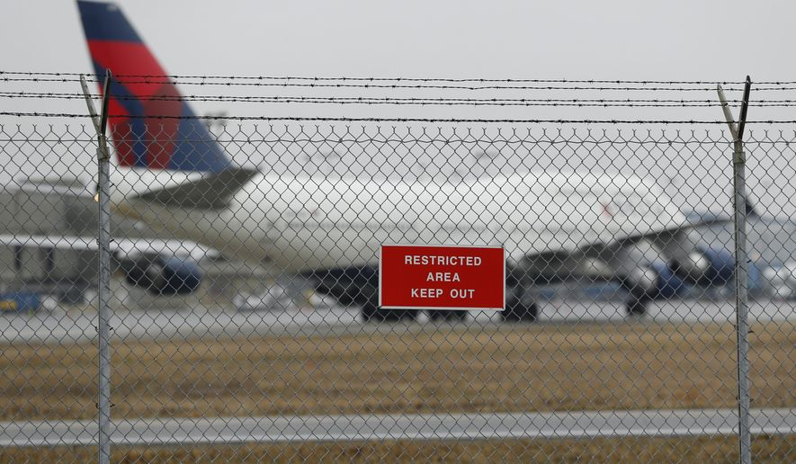 A sign is shown posted on a perimeter fence near Delta 747 aircraft taxiing at the Detroit Metropolitan Airport in Romulus, Mich., Thursday, April 9, 2015. The security fences and perimeter gates at Detroit Metropolitan Airport have been breached four times in the past two years, an Associated Press investigation shows. Nationally, at least 272 such breaches occurred at 31 major U.S. airports since the start of 2004. (AP Photo/Paul Sancya)