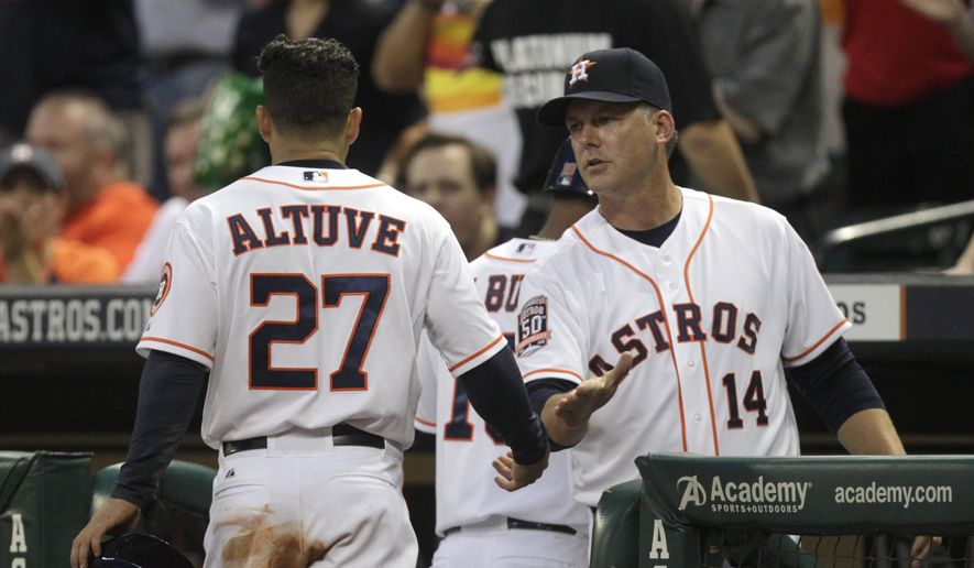 Houston Astros' manager A.J. Hinch congratulates Jose Altuve after he scored on a George Springer single during the sixth inning of an opening day baseball game against the Cleveland Indians, Monday, April 6, 2015, in Houston. (AP Photo/Patric Schneider)