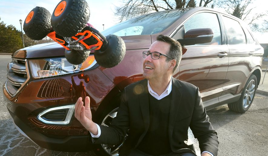 "Ford car designer Kevin George tosses the Ricochet, a flipping, double sided R/C toy outside the Ford campus in Dearborn, Mich., on March 23, 2015.  George, exterior design manager for the 2015 Edge crossover, came to Ford through an unusual route: the toy business. For a dozen years, he designed some of the most beloved toys on kids' wish lists,  Ricochet, ""Jurassic Park"" movie figures, ""Batman"" vehicles, NASCAR models, for Kenner before he realized his life's dream and crossed over to the auto industry in 2001 to sculpt cars. (AP Photo/Detroit News, Daniel Mears)  DETROIT FREE PRESS OUT; HUFFINGTON POST OUT"
