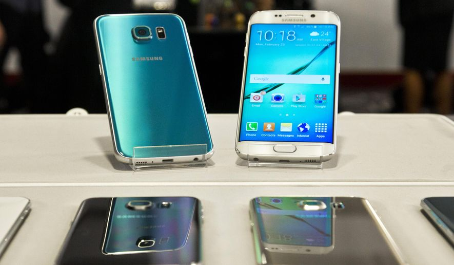 FILE - In this Feb. 23, 2015 file photo, two new Samsung phones, the Galaxy S6, top left, and Galaxy S6 Edge, top right, are on display at a special press preview in New York. Samsung's new Galaxy phones make their general U.S. debut on Friday, April 10, 2015. (AP Photo/Bebeto Matthews, File)