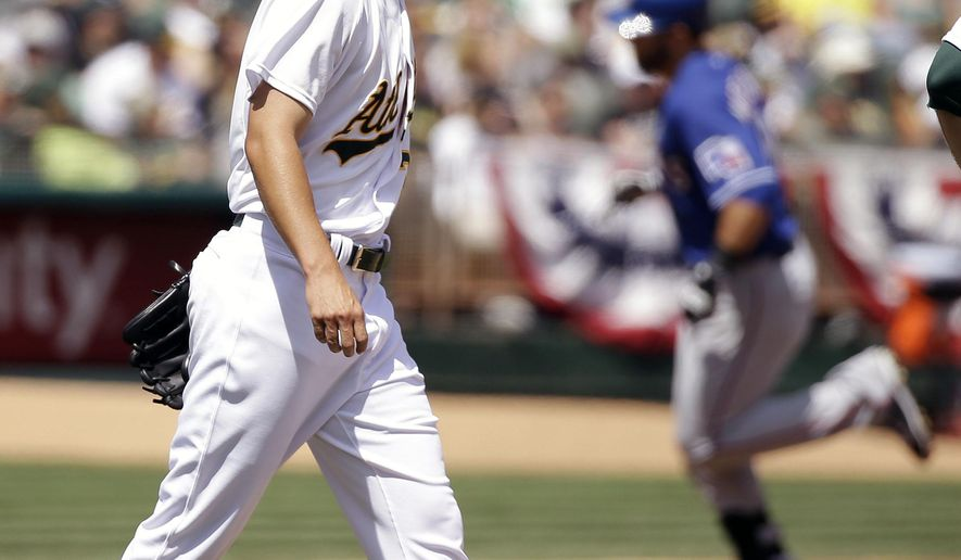 Oakland Athletics starting pitcher Kendall Graveman, left, walks back to the mound after giving up a two run homer to Texas Rangers' Mitch Moreland in the third inning of their baseball game Thursday, April 9, 2015, in Oakland, Calif. (AP Photo/Eric Risberg)