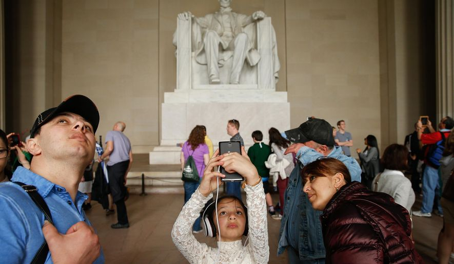 ADVANCE FOR USE SUNDAY, APRIL 12, 2014 AND THEREAFTER - In this Tuesday, April 7, 2015 photo, Asal Amrieva of New York, N.Y., center, takes a photograph while visiting the Lincoln Memorial in Washington. A century and a half after Lincoln was killed, people continue to connect with him in almost personal terms, while searching anew for his relevance to the Republic he left behind. (AP Photo/Andrew Harnik)