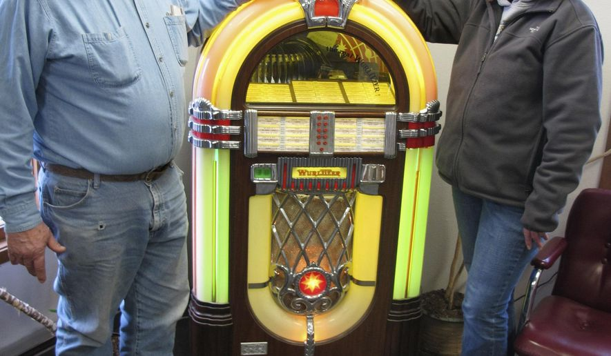 In this Wednesday, April 8, 2015 photo, Delon and Julie Cahoon show off a Wurlitzer juke box inside her business, Julie's Radio Ranch, in Fargo, N.D. The Cahoons recently purchased a farmstead near Arthur, N.D., where they plan to continue a 63-year-old tradition of barn dances. The couple will host their first dance Friday, April 10. (AP Photo/Dave Kolpack)