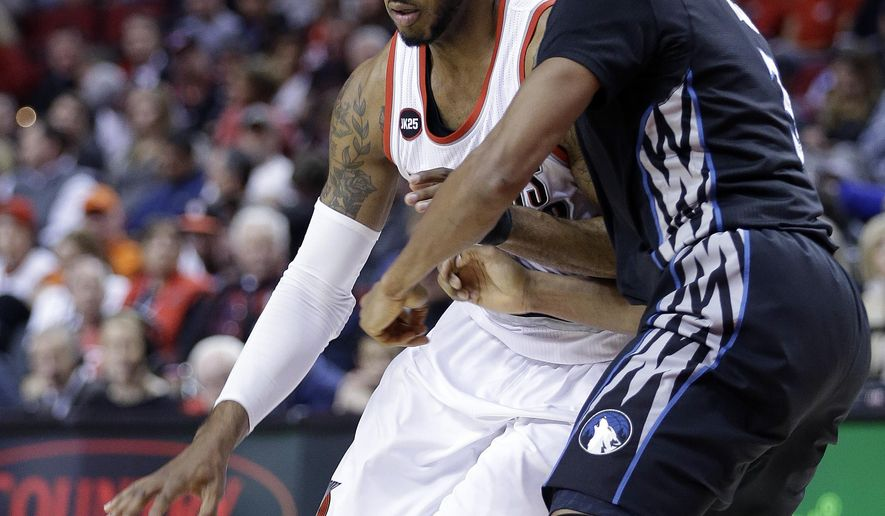 Portland Trail Blazers forward LaMarcus Aldridge, left, drives on Minnesota Timberwolves guard Kevin Martin during the first half of an NBA basketball game in Portland, Ore., Wednesday, April 8, 2015.  (AP Photo/Don Ryan)