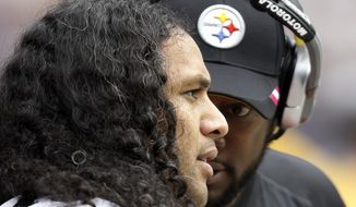 FILE - In this Oct. 2, 2011, file photo, Pittsburgh Steelers coach Mike Tomlin, right, talks to strong safety Troy Polamalu during an NFL football game against the Houston Texans in Houston. Polamalu's iconic football career is over. The eight-time Pro Bowl safety told the Uniontown Herald-Standard he informed Steelers chairman Dan Rooney on Thursday night, April 9, 2015, he will retire rather than return for a 13th season. (AP Photo/Eric Gay, File)
