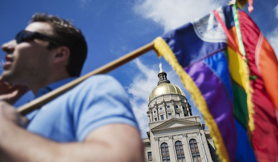 """The dome of the Capitol stands in the background as Stephen Saras, of Atlanta, holds a rainbow colored flag during a rally against a contentious """"religious freedom"""" bill, Tuesday, March 17, 2015, in Atlanta. The Georgia Senate gave decisive approval to the bill, one of a wave of measures surfacing in at least a dozen states that critics say could provide legal cover for discrimination against gays and transgender people. (AP Photo/David Goldman)"""