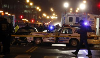 Law enforcement officers investigate the scene involving at least one wrecked DC Metro police car, in the 1100 block of H Street NE, Thursday, April 9, 2015 in Washington. Police say a man who kidnapped his wife shot a guard at the U.S. Census Bureau headquarters in Maryland before leading police on a chase into Washington, D.C., that ended with the suspect and an officer wounded. (AP Photo/Alex Brandon)