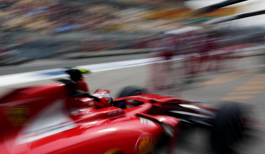 Ferrari driver Kimi Raikkonen of Finland returns to his garage during the second practice session for the Chinese Formula One Grand Prix at Shanghai International Circuit in Shanghai, China, Friday, April 10, 2015. (AP Photo/Andy Wong)