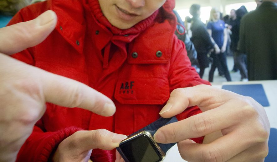 Ricky Lea examines Apple's new watch, which could only be bought as a pre-order online, Friday, April 10, 2015, in New York.  The first new gadget under CEO Tim Cook is selling in eight countries and Hong Kong, with shipments scheduled to start April 24. (AP Photo/Bebeto Matthews)