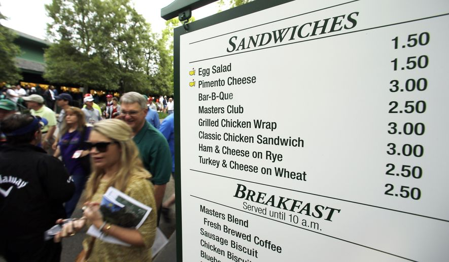 In this file photo taken Monday, April 6, 2015, patrons walk past a vendor sign during a practice round for the Masters golf tournament, in Augusta, Ga. At a time when buying a hot dog and a beer at any big event can mean a pricey tab and a credit card, Augusta National makes it easy to fill up in possibly the best value meal deal in all of sports with a menu that is pure South. (AP Photo/Chris Carlson)