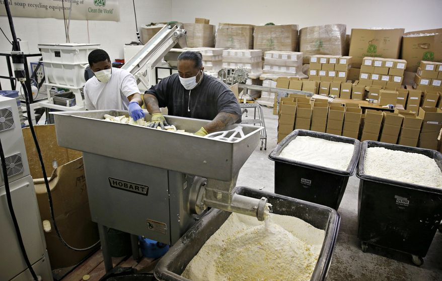 In this March 20, 2015, photo, Jabir Hennix, left, and Sia Leleua grind up used bars of soap at Clean the World in Las Vegas. The non-profit  initiative recycles soap from hotels to distribute in developing countries. (AP Photo/John Locher)