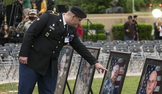Purple Heart recipient Pfc. James Armstrong, touches the image of Cpt. John Gaffaney, as he looks at pictures of those killed in the 2009 Fort Hood shooting prior to a Purple Heart ceremony held at Fort Hood, Texas. (AP Photo/Austin American-Statesman, Rodolfo Gonzalez, Pool)