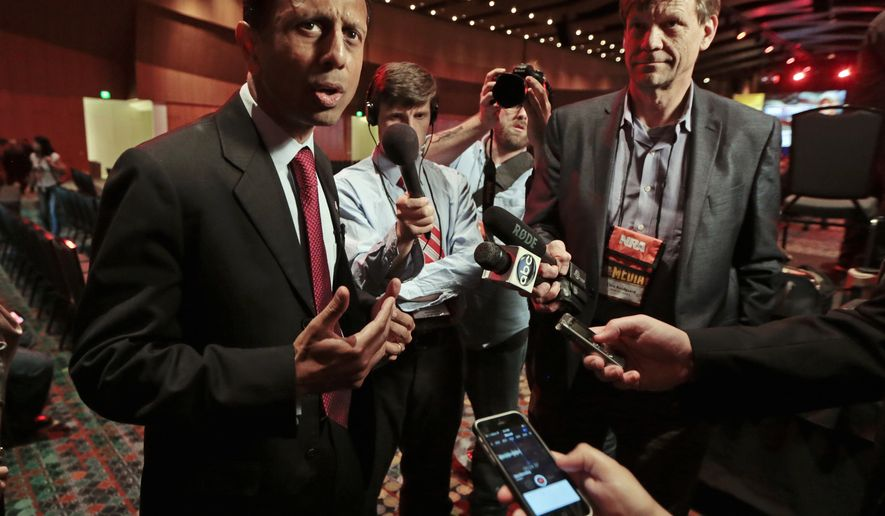 Louisiana Gov. Bobby Jindal, left, talks with reporters at the National Rifle Association convention Friday, April 10, 2015, in Nashville, Tenn. (AP Photo/Mark Humphrey)