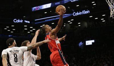 Washington Wizards guard Ramon Sessions (7) goes to the basket past Brooklyn Nets guard Deron Williams (8) and center Brook Lopez during the first half of an NBA basketball game, Friday, April 10, 2015, at  New York.  (AP Photo/Mary Altaffer)