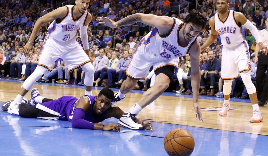 Oklahoma City Thunder center Steven Adams (12) and Sacramento Kings forward Carl Landry, bottom, go after the ball during the second quarter of an NBA basketball game in Oklahoma City, Friday, April 10, 2015. (AP Photo/Alonzo Adams)