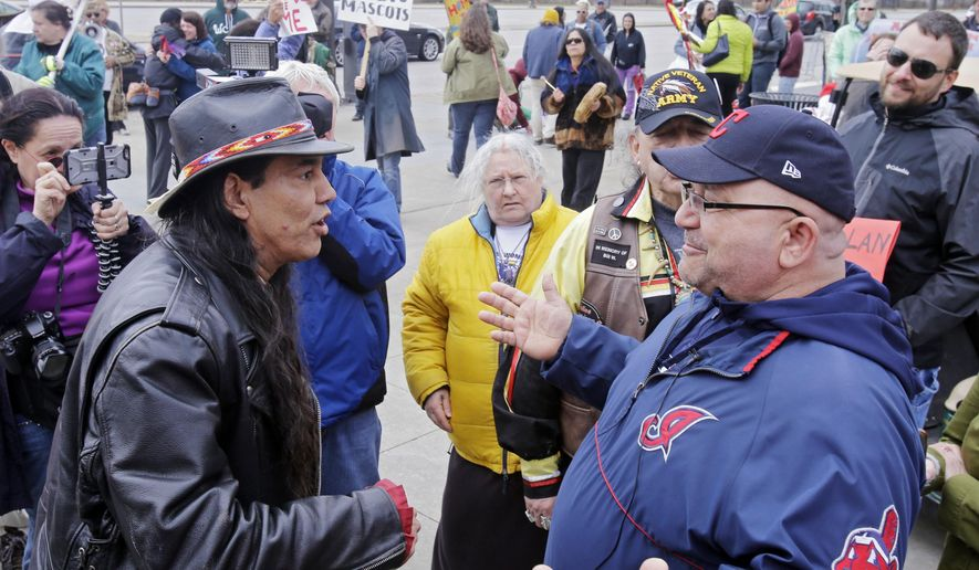 Philip Yenyo, left, executive director of the American Indians Movement for Ohio, talks with a Cleveland Indians fan before a baseball game against the Detroit Tigers Friday, April 10, 2015, in Cleveland. A small group demonstrated against the Indians' Chief Wahoo mascot outside the ballpark. (AP Photo/Mark Duncan)