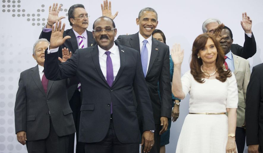 U.S. President Barack Obama, center, waves as he joins other world leaders during the official Leaders' Photo at the Summit of the Americas in Panama City, Panama, Saturday, April 11, 2015. Also in the group are from left to right, El Salvador's President Salvador Sanchez Ceren, Saint Lucia's Prime Minister Kenny Anthony, Antigua and Barbuda's Prime Minister Gaston A. Browne, Argentina's President Cristina Fernandez, and Grenada's Prime Minister Keith Mitchell. (AP Photo/Pablo Martinez Monsivais)