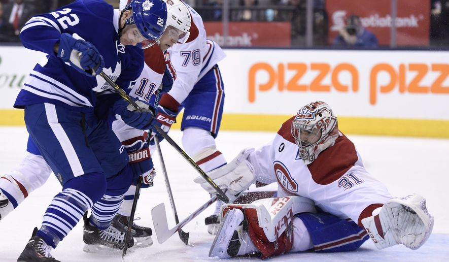 Montreal Canadiens goalie Carey Price makes a save on Toronto Maple Leafs' Zach Sill (22) as Canadiens' Brendan Gallagher (11) and Andrei Markov (79) defend during the second period of an NHL hockey game, Saturday, April 11, 2015 in Toronto. (Frank Gunn/The Canadian Press via AP)   MANDATORY CREDIT