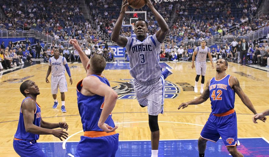 Orlando Magic's Dewayne Dedmon (3) grabs an offensive rebound against the New York Knicks, from left, Langston Galloway, Cole Aldrich and Lance Thomas (42) during the first half of an NBA basketball game, Saturday, April 11, 2015, in Orlando, Fla. (AP Photo/John Raoux)
