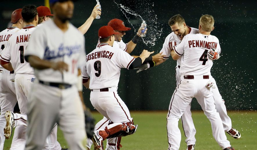 Arizona Diamondbacks' Ender Inciarte is hugged by Cliff Pennington (4) as they celebrate Inciarte's walk-off RBI single, after a baseball game against the Los Angeles Dodgers, Friday, April 10, 2015, in Phoenix. The Diamondbacks won 4-3. (AP Photo/Matt York)