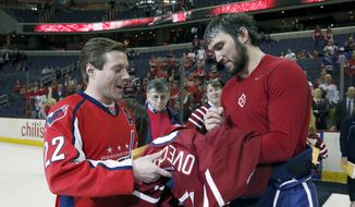 Washington Capitals left wing Alex Ovechkin (8), from Russia, right, signs a jersey he gave to Tom Clinch, from Potomac, Md., during a fan appreciation event after an NHL hockey game against the New York Rangers, Saturday, April 11, 2015, in Washington. The Rangers won 4-2. (AP Photo/Alex Brandon)